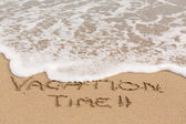 Vacation Time written in sand with sea surf — Stock fotografie
