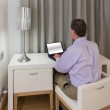 Man at white desk and chairs in hotel — Stock Photo