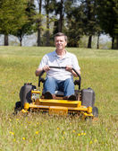 Senior man on zero turn lawn mower on turf — Stock Photo