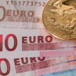 Stock Photo: Gold coins on ten and twenty euro notes bills