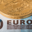 Stock Photo: Gold coins on euro note bill with coins