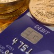 Stock Photo: Gold coins on chip and pin debit card