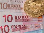 Gold coins on ten and twenty euro notes bills — Stock Photo
