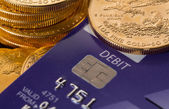 Gold coins on chip and pin debit card — Stock Photo