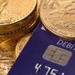 Gold coins on chip and pin debit card — Stockfoto