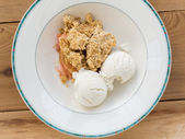 Traditional british apple crumble pie in dish with ice cream — Stock Photo