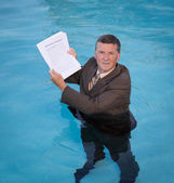 Senior man holding mortgage loan document in water — Stock Photo