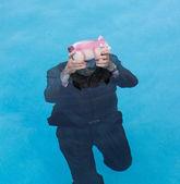 Senior man holding piggy bank above water — Stock Photo