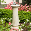 Concrete stone sundial in flower bed — Stock Photo