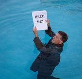 Senior man holding help me paperwork in water — Stock Photo