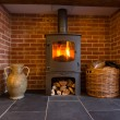 Wood burning stove in brick fireplace — Stock Photo