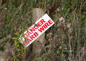 Danger barb wire sign on post — Stock Photo