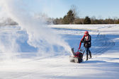 Senior woman clearing drive with snowblower — Stock Photo