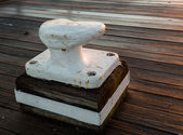 Large metal bollard on wooden decking — Stock Photo