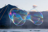 Man making large soap bubbles on beach — Stock Photo