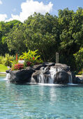 Hotel swimming pool with waterfall — Stock Photo