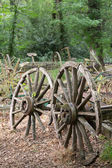 Two old wooden cartwheel against wood cart — Foto Stock