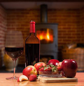 Red wine and fruit in front of burning fire — Stok fotoğraf