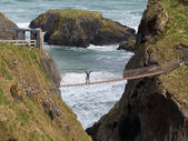 Young woman on rope bridge Ireland — Stock Photo