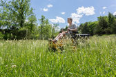 Senior man on zero turn lawnmower in meadow — Stock Photo