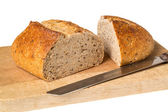 Artisan whole wheat bread on breadboard — Stock Photo