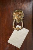 Envelope placed under door knocker — Stock Photo