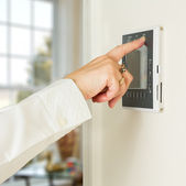 Caucasian lady pressing modern thermostat — Stock Photo