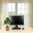 Small bonsai tree on plain office desk with monitor — Stock Photo #49380251