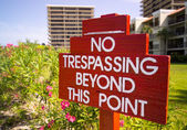 No Trespassing sign in red by flower gardens — Stock Photo