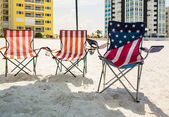 Three folding beach chairs under shade on beach — Stock Photo