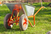 Wheel barrow on the grass in the garden — Zdjęcie stockowe
