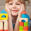 Child plays with toy blocks — Stock Photo #17497665