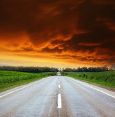 Asphalt road with cloudy sky and sunlight — Stock Photo