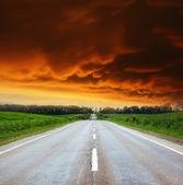 Carretera asfaltada con cielo nublado y la luz del sol — Foto de Stock