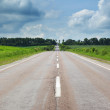 Road with cloudy sky and sunlight — Stock Photo