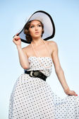 Portrait of pretty woman wearing white dress and straw hat in sunny warm weather day. — Stockfoto