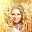 Young smiling woman in white dress standing in field — Stock Photo