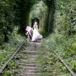 Happy bride walking along rail tracks  — Stock Video