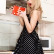Stock Photo: Beautiful young housewife in kitchen. girl holding pot.