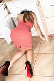 De vrouw stak haar hoofd in de wasmachine. — Stockfoto
