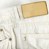 Fragment of white jeans with pure label for your text. — Foto de Stock