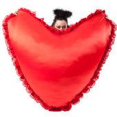Une fille avec un coeur sous la forme d'oreillers. — Photo