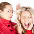 Stock Photo: Blonde girl whispering to a friend against white background.