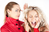 Blonde girl whispering to a friend against white background. — Foto Stock