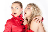 Blonde girl whispering to a friend against white background. — Stock Photo