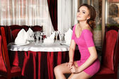 Girl in a short red dress sitting on a chair at a table in the restaurant. — Stock Photo