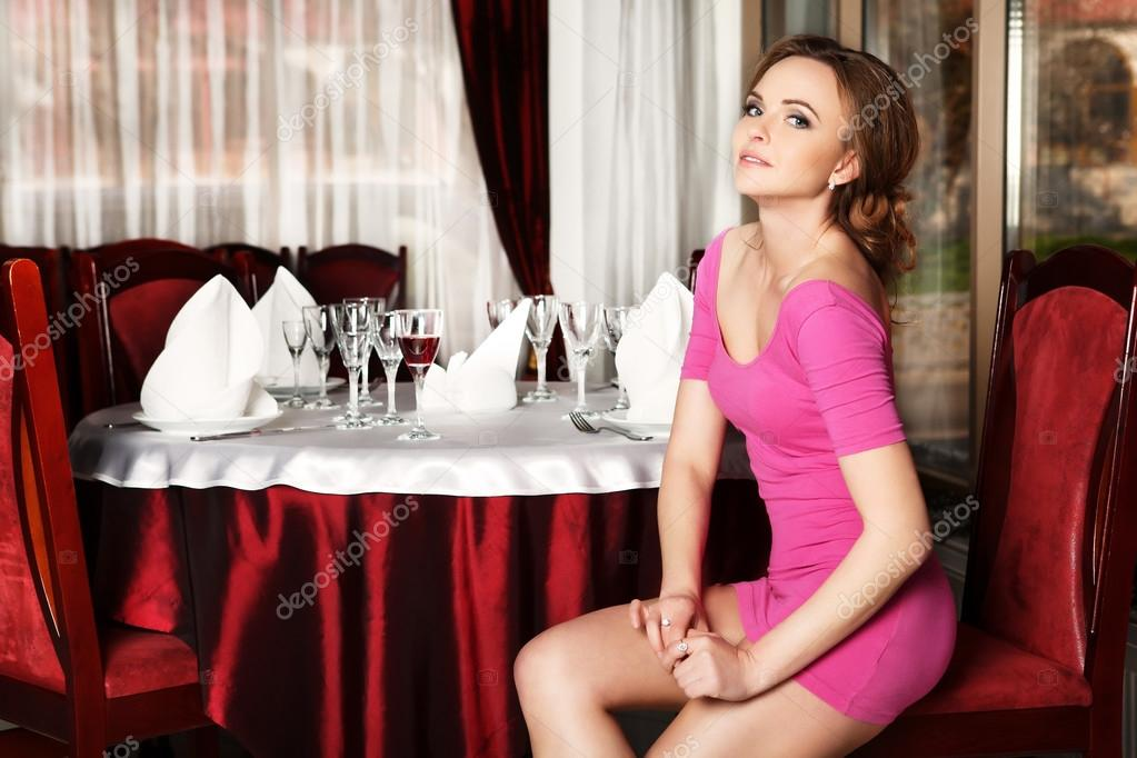 Girl In A Short Red Dress Sitting On A Chair At A Table In