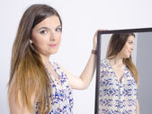 Real young woman looking in a mirror — Stock Photo