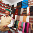 Small shop owner indian man at his souvenir store - Stock Photo