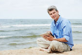 Young smiling man with tablet pc on seashore — Stock Photo